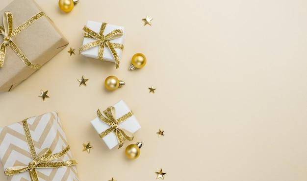 Coffrets cadeaux, décorations dorées et ornements sur fond beige pastel. fond de noël. mise à plat, vue de dessus, espace de copie.