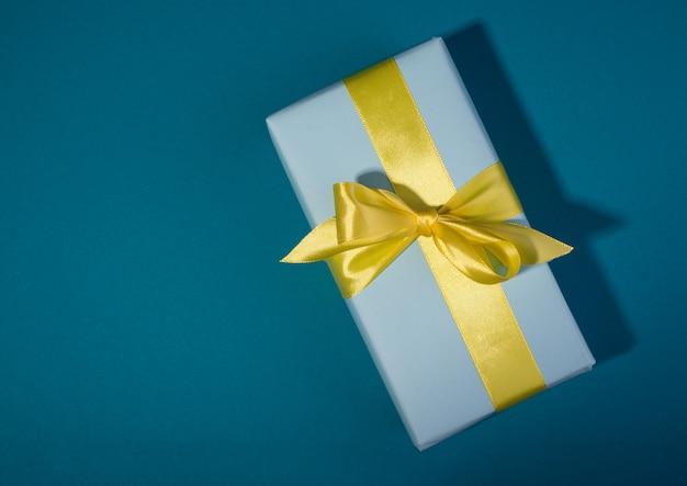 Coffrets cadeaux avec différentes couleurs sur un modèle de bannière. boîte cadeau bleue et arc jaune sur fond bleu audacieux.
