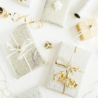 Coffrets cadeaux dorés, décorations sur surface blanche. mise à plat, vue de dessus