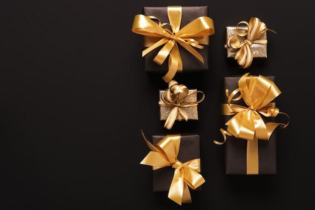 Coffrets cadeaux dorés emballés de manière festive sur fond noir. style plat. concept de vacances et de vendredi noir.