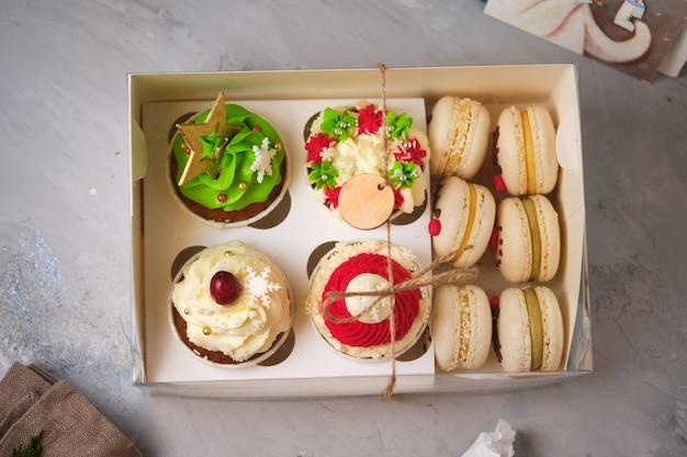 Coffrets cadeaux du nouvel an de bonbons. une boîte de cupcakes et macarons comme cadeau de noël. cupcakes avec crème au fromage à la crème et garniture au caramel aux arachides et gâteaux aux macarons avec garniture à la mandarine.