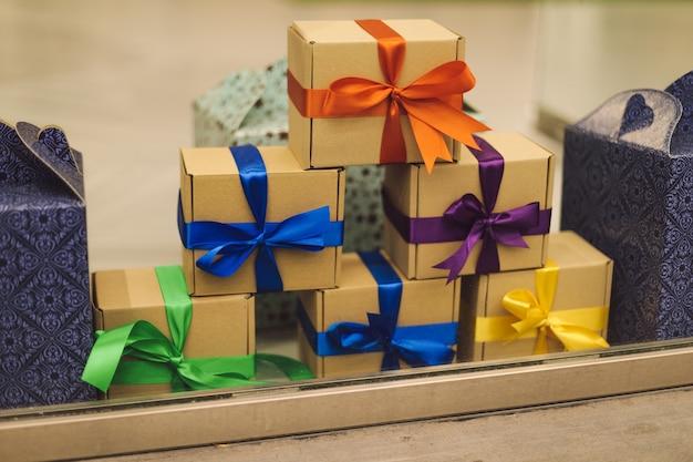 Des coffrets cadeaux emballés dans du papier et décorés de rubans colorés se dressent sur la surface. cadeaux et surprises. fêtes et décorations. mode de vie.