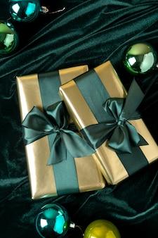 Coffrets cadeaux emballés dans du papier doré avec des rubans de satin vert marée