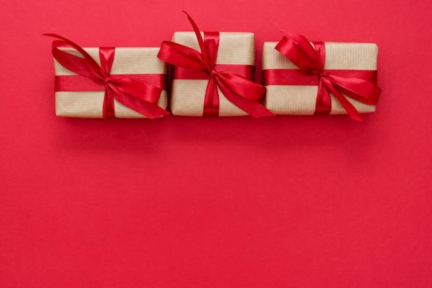 Coffrets cadeaux emballés avec du papier kraft et un arc rouge isolé sur fond rouge. mise à plat abstraite.