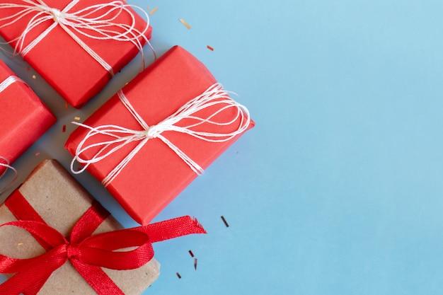 Coffrets cadeaux emballés rouges et kraft sur fond bleu avec espace de copie