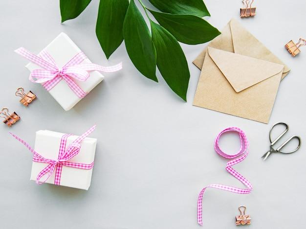 Coffrets cadeaux, enveloppe et feuilles vertes sur fond blanc