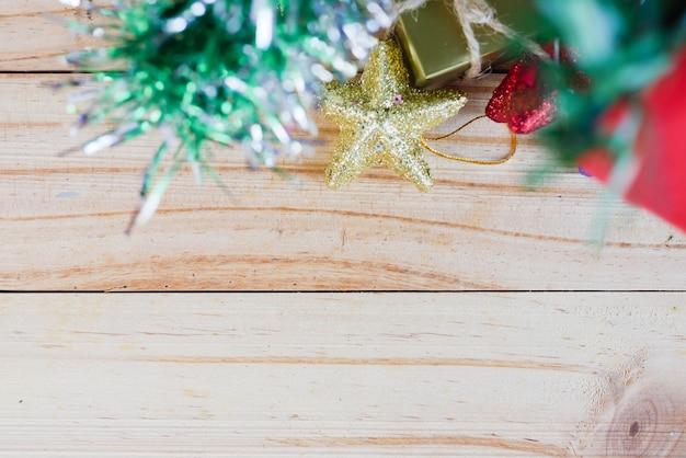 Coffrets cadeaux et étoiles sous l'arbre chirstmas sur la planche de bois