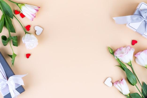 Coffrets cadeaux et fleurs eustoma pour la fête des mères ou d'autres vacances sur une surface beige, vue de dessus. espace copie