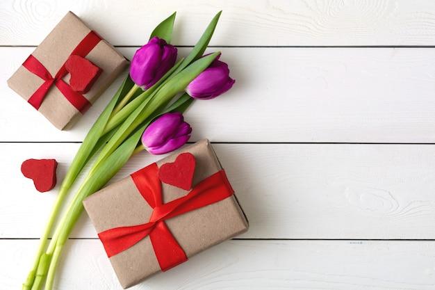 Coffrets cadeaux avec des fleurs sur un mur en bois blanc