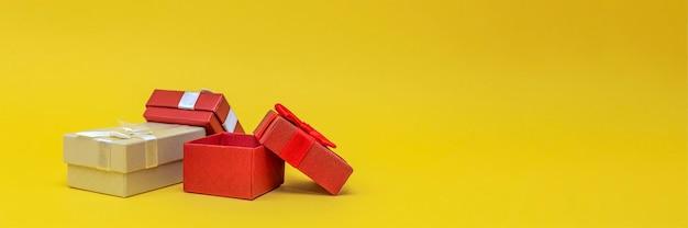 Coffrets cadeaux sur fond jaune, bannière. coffrets cadeaux rouges, boîte ouverte. carte postale pour l'impression, bannière avec place pour le texte. photo panoramique, grand format, espace vide pour félicitations ou design