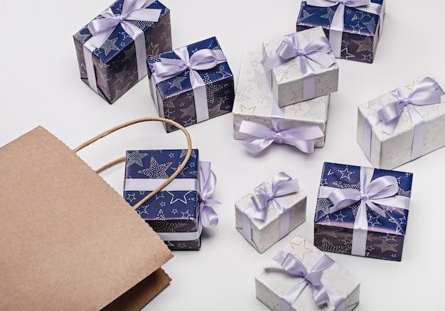 Coffrets cadeaux avec motifs, ruban lilas avec noeud, sac en papier. surprise pour différentes vacances sur un espace en bois. copiez l'espace.
