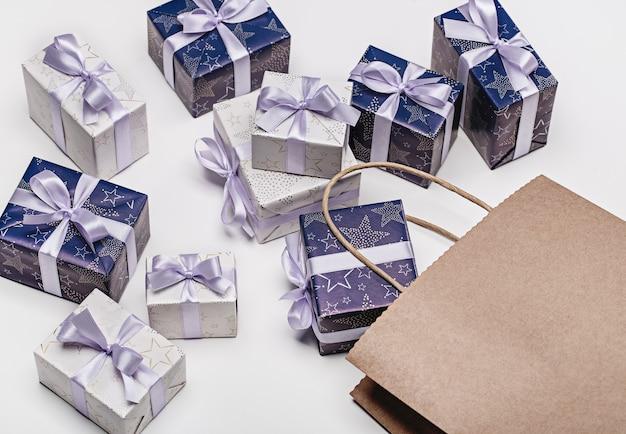 Coffrets cadeaux avec motifs, ruban lilas avec un noeud, sac en papier. surprise pour différentes vacances sur un espace en bois