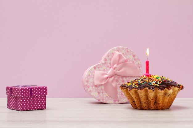 Coffrets cadeaux et muffin d'anniversaire savoureux avec glaçage au chocolat et caramel, décorés d'une bougie festive brûlante sur fond lilas. concept minimal de joyeux anniversaire.