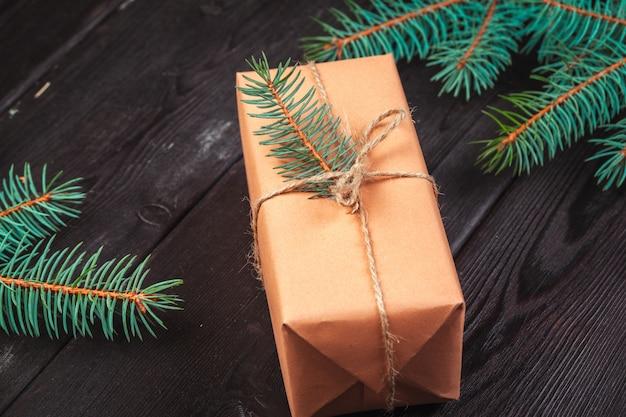 Coffrets-cadeaux de noël et branche de sapin sur une table en bois,