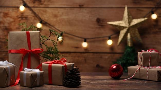 Coffrets cadeaux de noël et branches de sapin sur table en bois.
