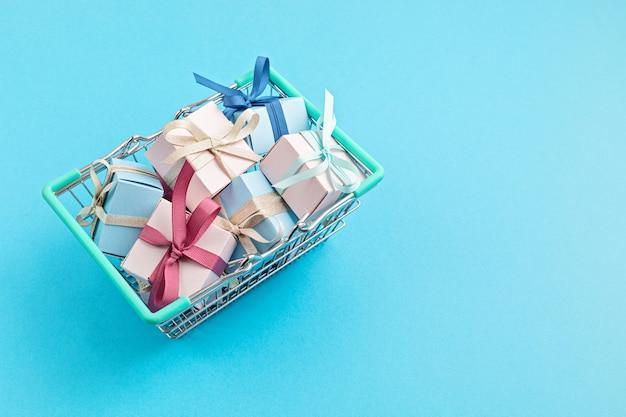 Coffrets cadeaux de noël dans le panier sur la surface bleue
