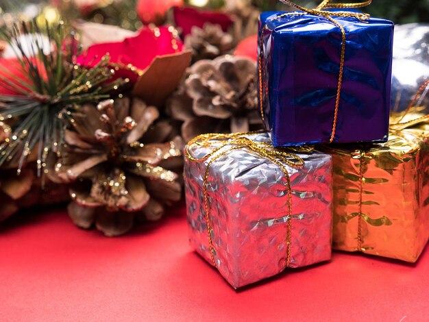 Coffrets cadeaux de noël emballés dans différentes couleurs sous l'arbre de noël sur fond rouge. . décoration intérieure festive.