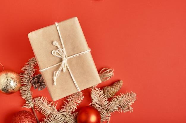 Coffrets cadeaux de noël emballés dans du papier kraft avec décoration sur fond rouge