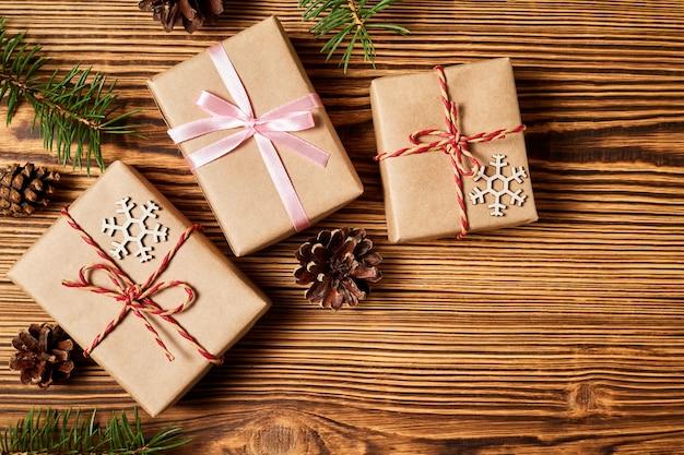 Coffrets cadeaux de noël sur fond de bois avec des pommes de pin et des branches de sapin avec espace de copie