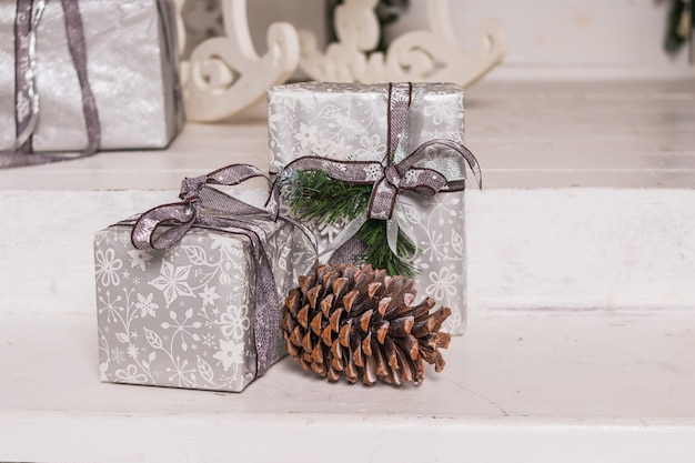 Coffrets-cadeaux de noël et noeuds d'argent sur fond blanc. carte de voeux de vacances. coffrets cadeaux emballés. nouvel an vacances. cadeaux faits à la main