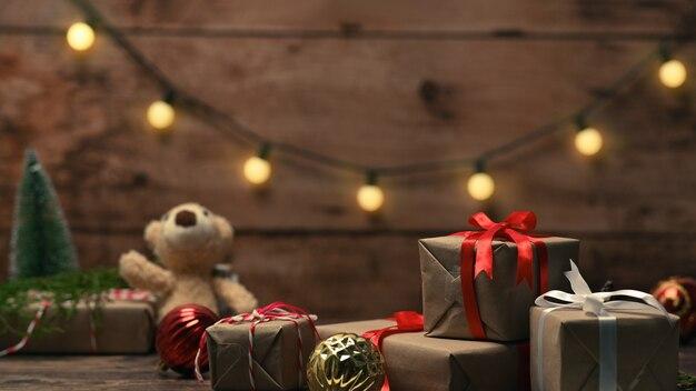 Coffrets cadeaux de noël, ours en peluche et décorations d'ornements de noël sur table en bois.