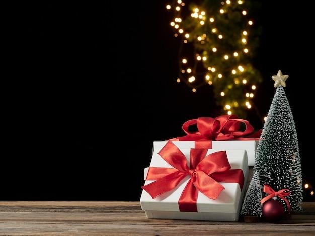 Coffrets cadeaux de noël et sapin sur table en bois contre les lumières de fête floues, espace pour le texte