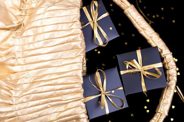 Coffrets cadeaux noirs avec ruban d'or sortent du sac d'or sur fond brillant