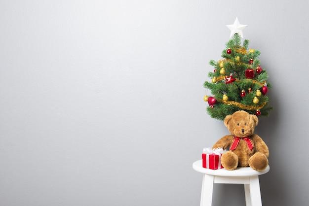 Coffrets cadeaux, ours en peluche et petit arbre de noël décoré sur une chaise de tabouret