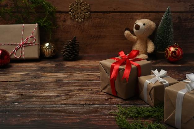 Coffrets cadeaux, ours en peluche, pommes de pin et branches de sapin sur table en bois.