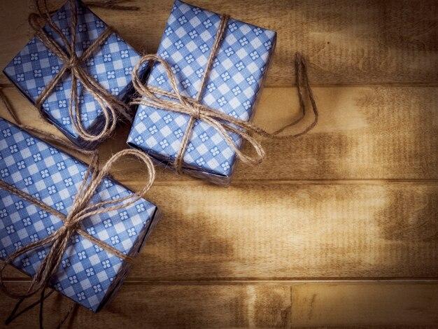 Coffrets cadeaux en papier bleu sur la table en bois