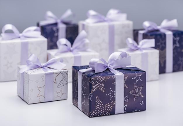 Coffrets cadeaux en papier élégant avec rubans et nœuds lilas, sur un espace lilas. joyeuses fêtes