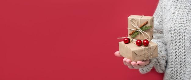 Coffrets cadeaux en papier kraft et décor en mains de femmes sur fond rouge. bannière panoramique lumineuse, tendance, nouvel an, espace de copie. offrir des cadeaux pour noël, vente, remises.