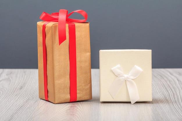 Coffrets cadeaux sur planches de bois et fond gris. concept de jour de célébration.
