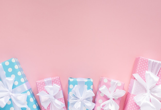 Coffrets cadeaux rose et bleu à pois avec ruban blanc et arc sur un mur rose, mise à plat, vue du dessus