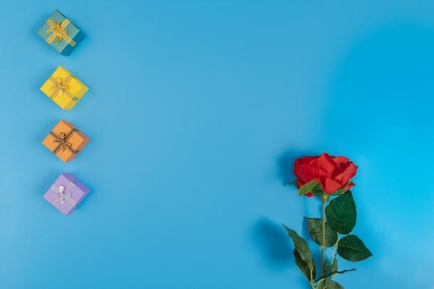 Coffrets cadeaux et une rose rouge sur fond bleu