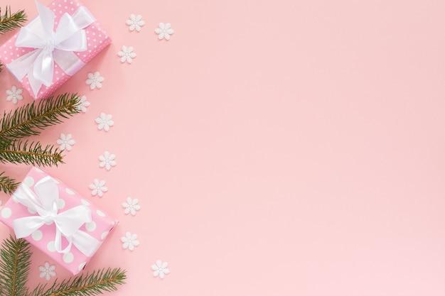 Coffrets cadeaux roses à pois avec ruban blanc et arc et branches d'épinette sur un rose avec des flocons de neige