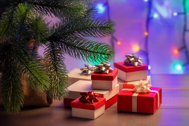 Coffrets cadeaux rouges et blancs sous le sapin de noël.