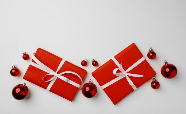 Coffrets cadeaux rouges et boules de noël sur fond blanc vue de dessus