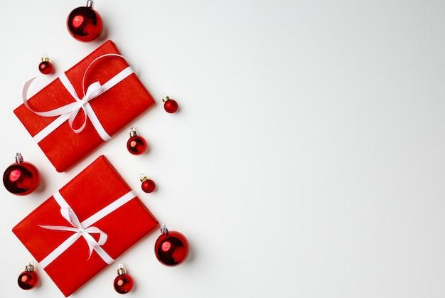 Coffrets cadeaux rouges et boules de noël sur fond blanc
