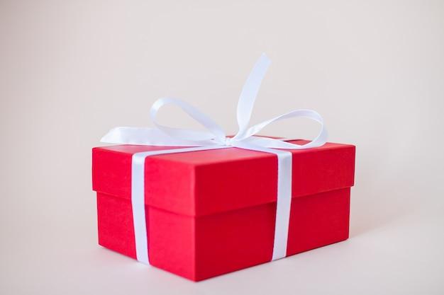 Coffrets cadeaux rouges de différentes tailles attachés avec un ruban de satin blanc