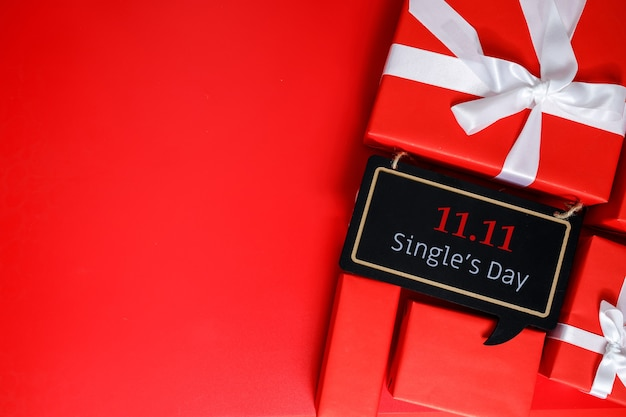 Les coffrets cadeaux rouges sur fond rouge avec espace de copie pour le texte 11.11 vente du jour unique.