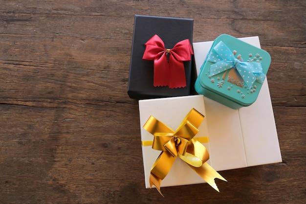 Coffrets cadeaux avec ruban sur fond en bois marron, vue de dessus avec copie