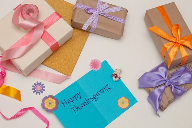 Coffrets cadeaux avec des rubans et des arcs lumineux sur fond blanc carte postale bleue, argent, billets d'un dollar, euros, lieu de copie, vue de dessus, thanksgiving, vacances, mise à plat