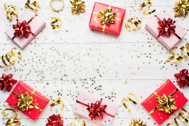 Coffrets cadeaux avec des rubans et des arcs d'or, des étoiles de confettis sur fond blanc. espace copie mise à plat. carte de voeux pour fête d'anniversaire, fête des mères de mariage de noël.