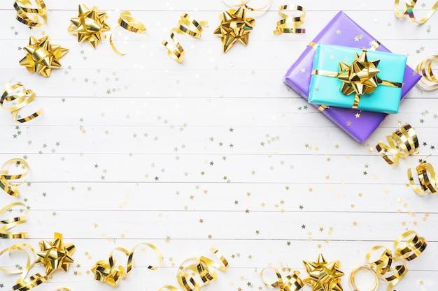 Coffrets cadeaux avec des rubans et des arcs d'or, des étoiles de confettis sur fond blanc.