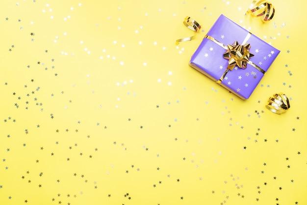 Coffrets cadeaux avec rubans et noeuds en or, étoiles de confettis sur fond jaune. espace copie mise à plat. carte de voeux pour fête d'anniversaire, fête des mères de mariage de noël.
