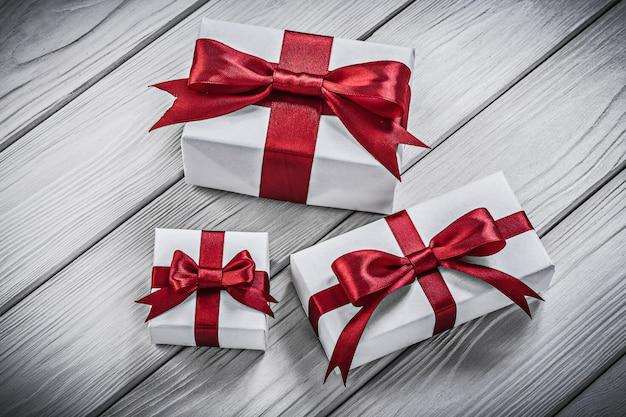 Coffrets cadeaux avec des rubans rouges sur le concept de vacances de planche de bois