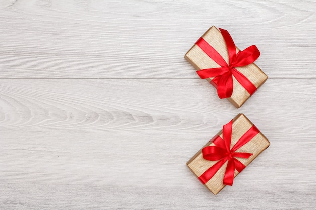Coffrets cadeaux avec des rubans rouges sur des planches en bois gris. notion de carte de voeux. vue de dessus avec espace de copie.