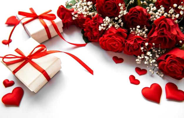 Coffrets cadeaux de la saint-valentin et bouquet de roses rouges sur une surface blanche
