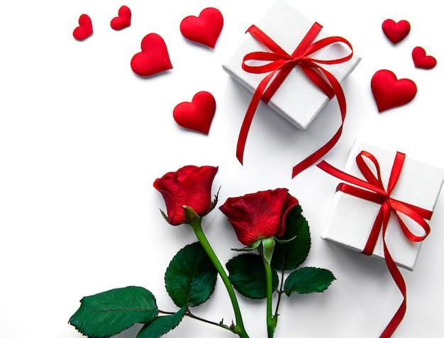 Coffrets cadeaux de la saint-valentin et roses rouges sur une surface blanche